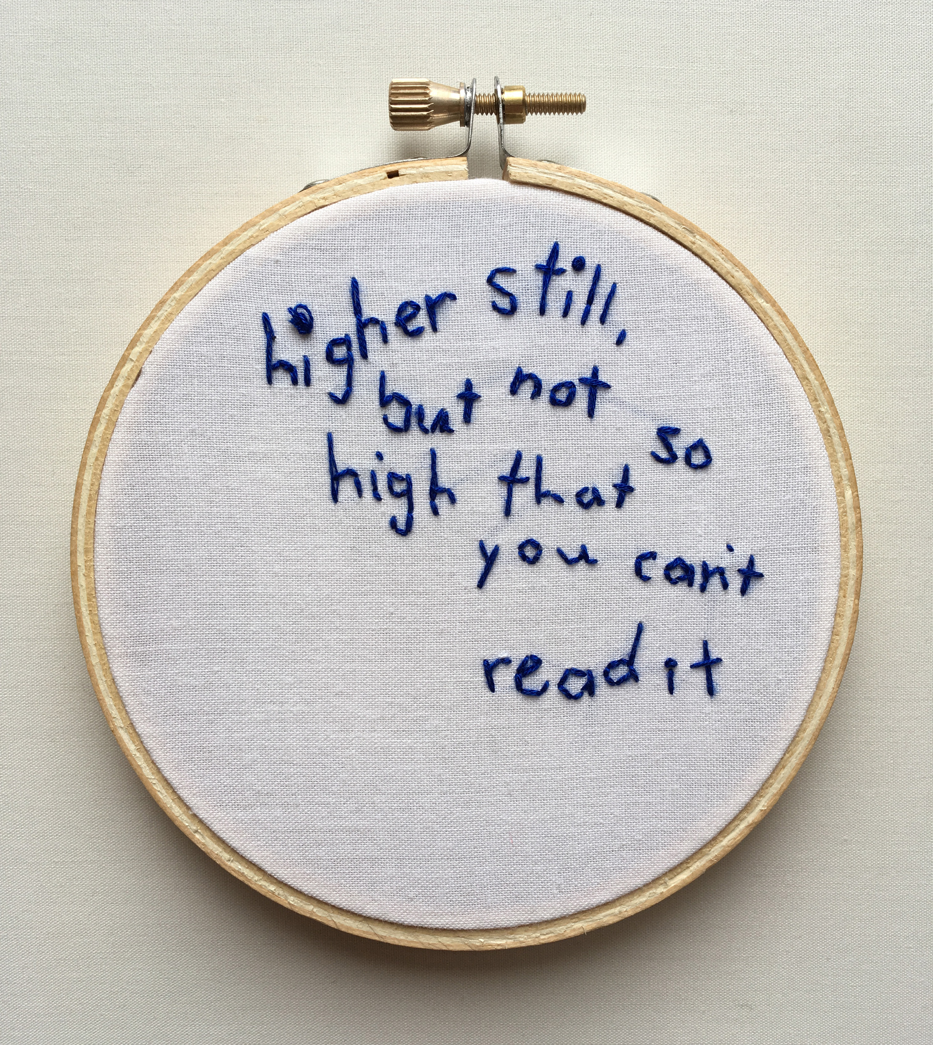 """An embroidery of the text """"higher still, but not so high that you cant read it"""" on white fabric stretched over a hoop."""