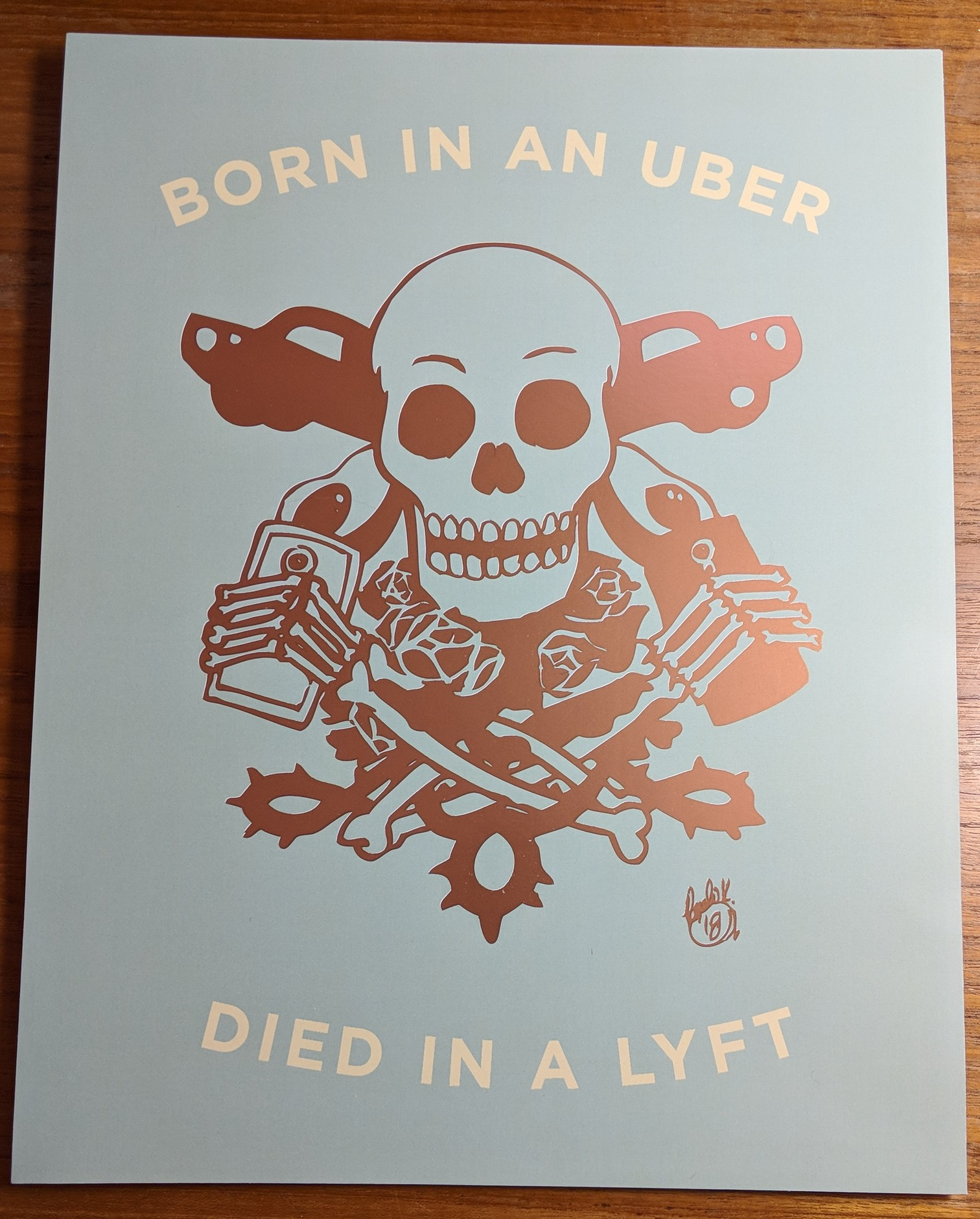 A skeleton holding two smartphones, surrounded by cars, avocados and roses. Text says BORN IN AN UBER, DIED IN A LYFT.
