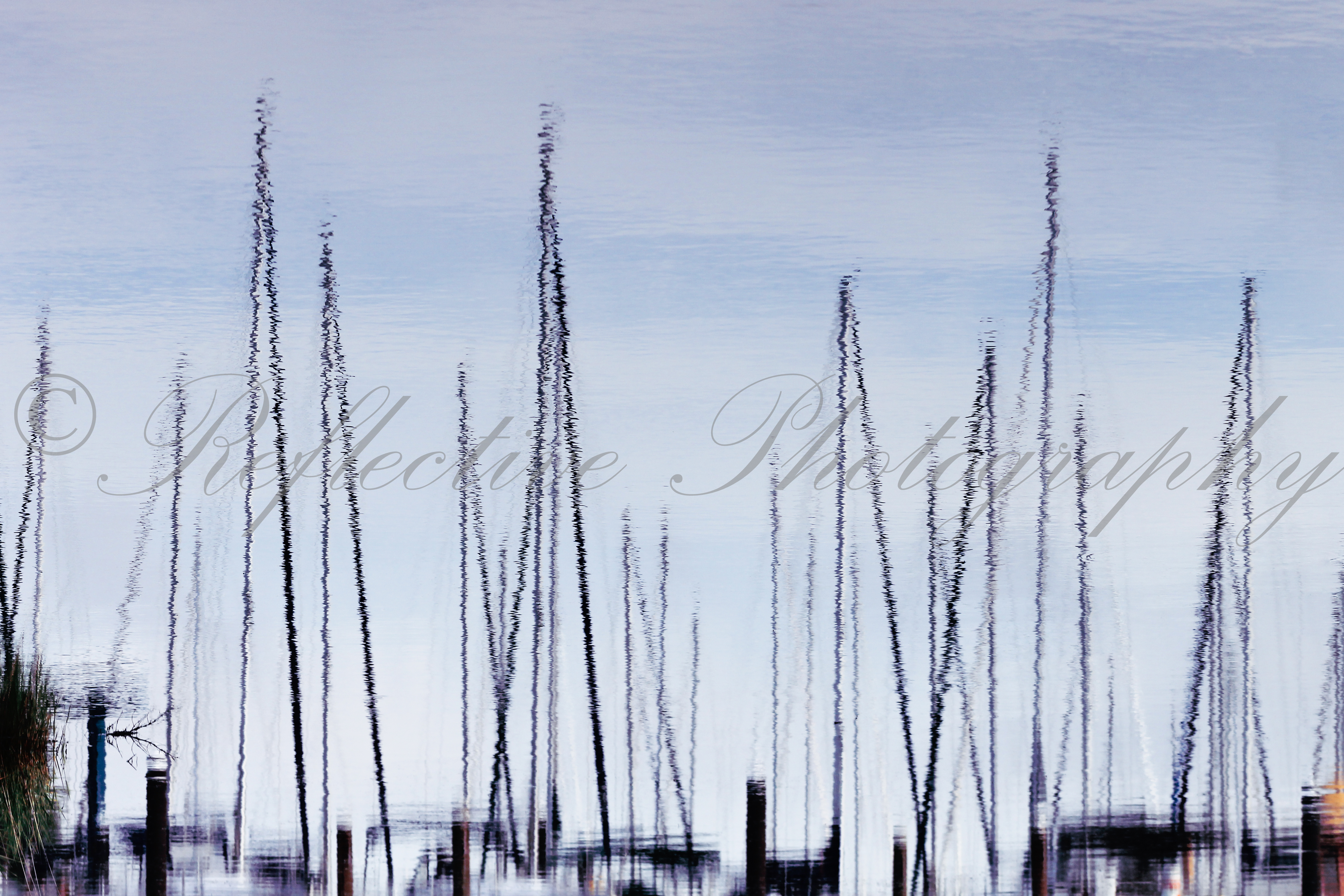 Photograph of boat masts reflected in water