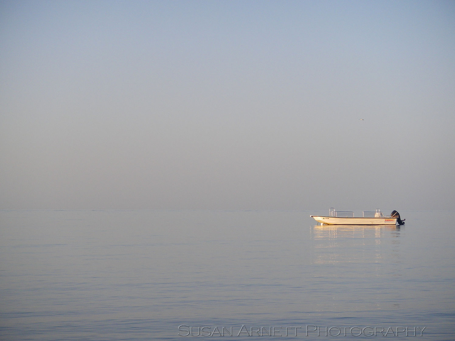 A lone small boat floats on the glassy ocean, reflecting the sunrise, as the ocean and sky meld together seamlessly