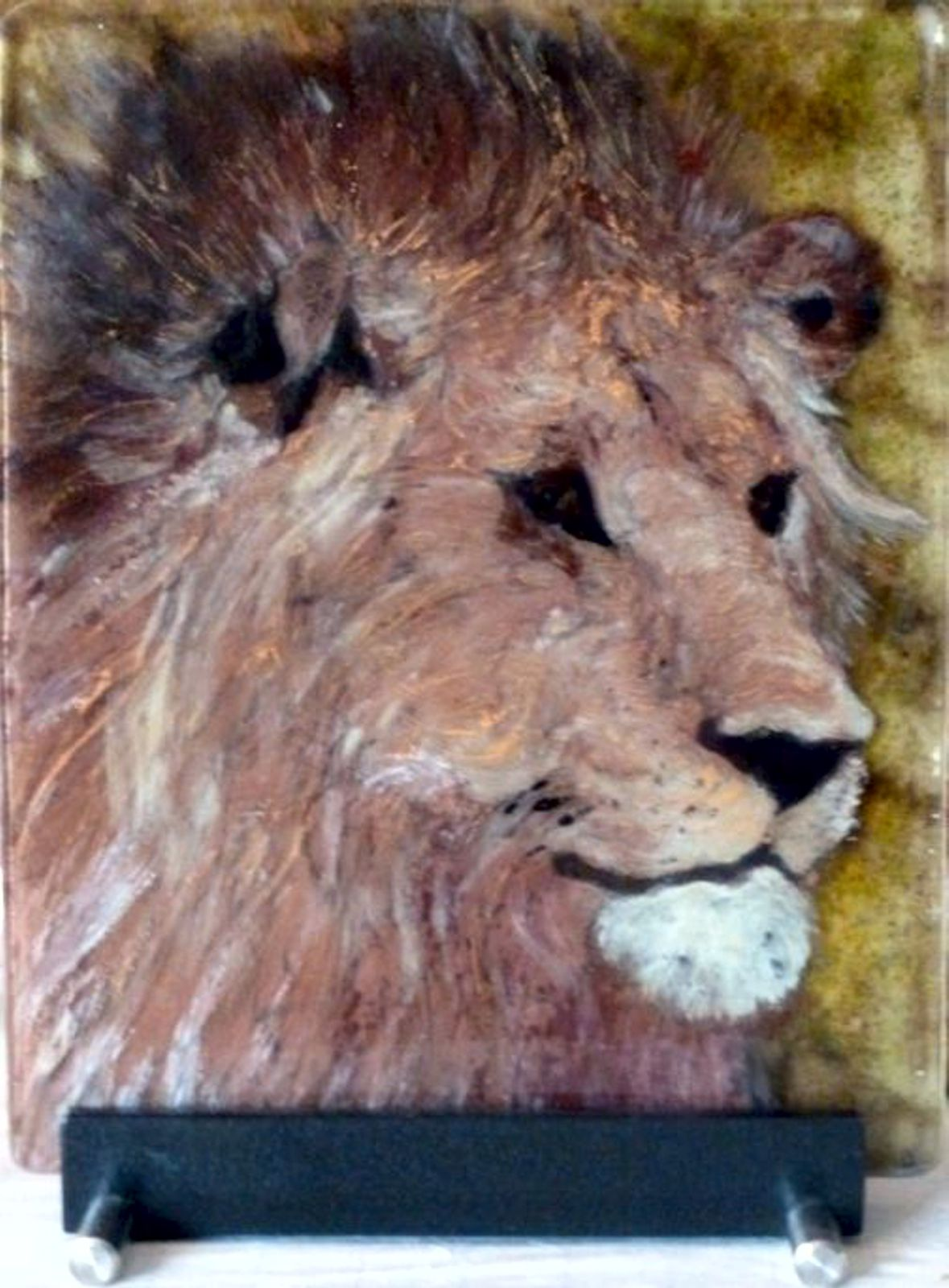 Lion King is created by using frits and glass paint on float glass.  Three panels of glass are used and kiln fired.