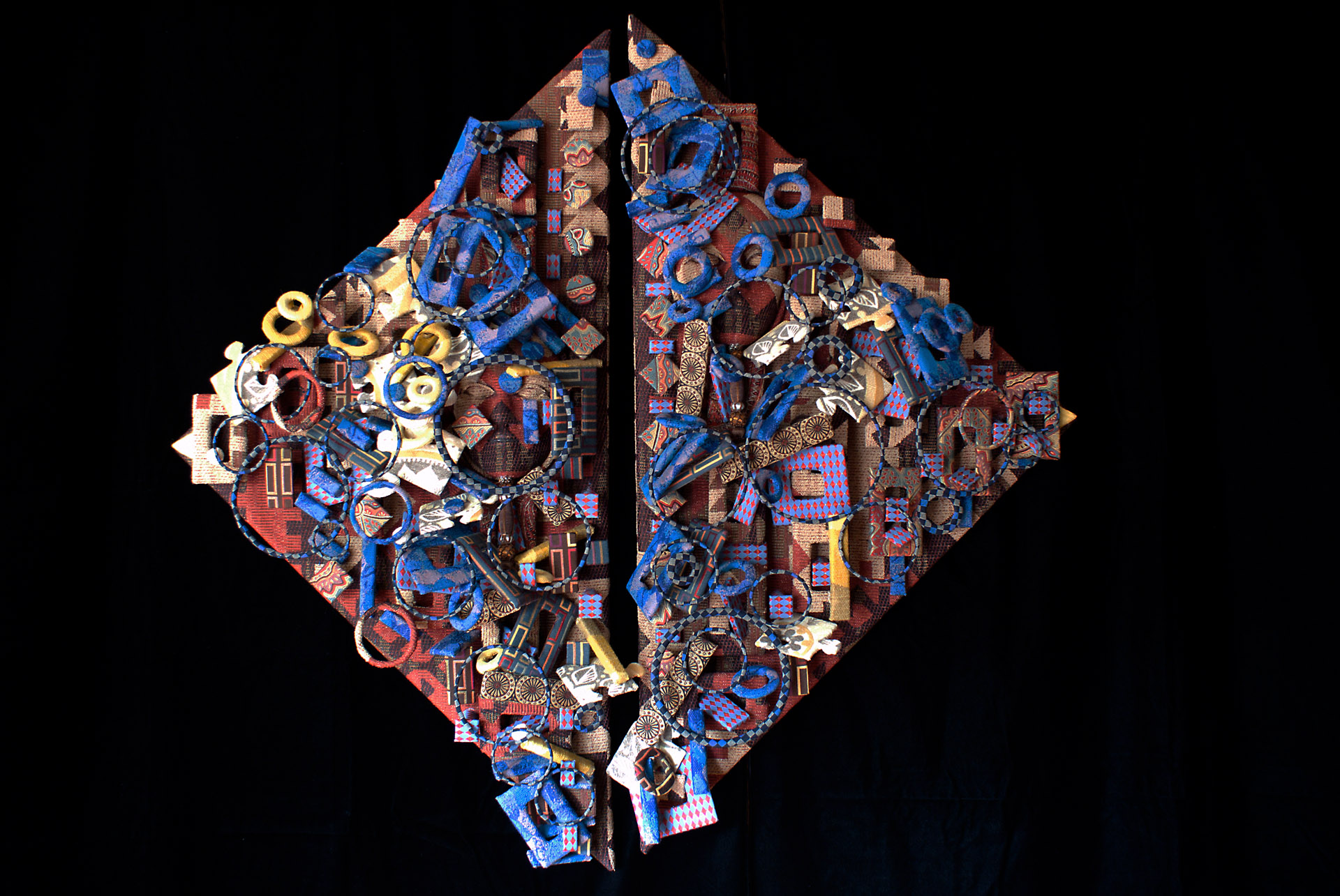 Fabric stretched over triangle wooded frames, layered with additional fabric covered mixed media with 2 embedded faces.