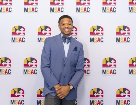 2020 Maryland State POL Champion Randolph Smith stands in front of a step and repeat banner with the MSAC Logo.