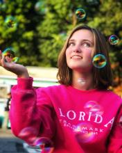 2021 Maryland State POL Champion Kate Maerten looks up at the sky in awe of bubbles surrounding them.