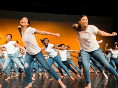Synchronized dancers on stage in jeans