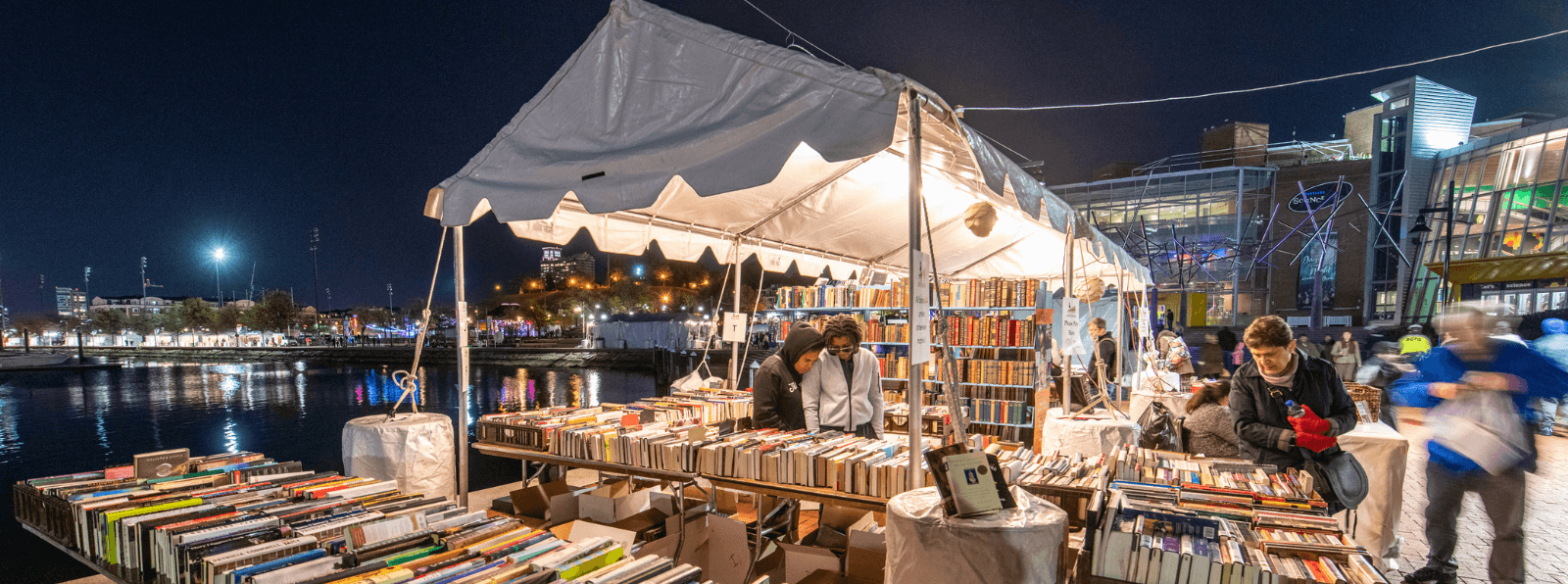 People browsing books at an outdoor tent next to a body of water