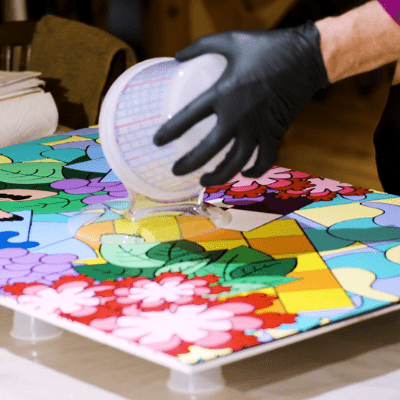 A person in gloves pouring clear liquid onto a red, green, yellow, orange, blue, and purple painting