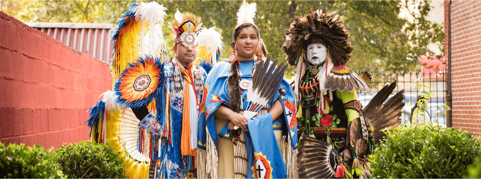 Three people in Lumbee, Tusarora, and Powhatan dress face the camera