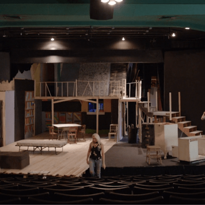 Four people working on a stage setting up a play in an empty theater