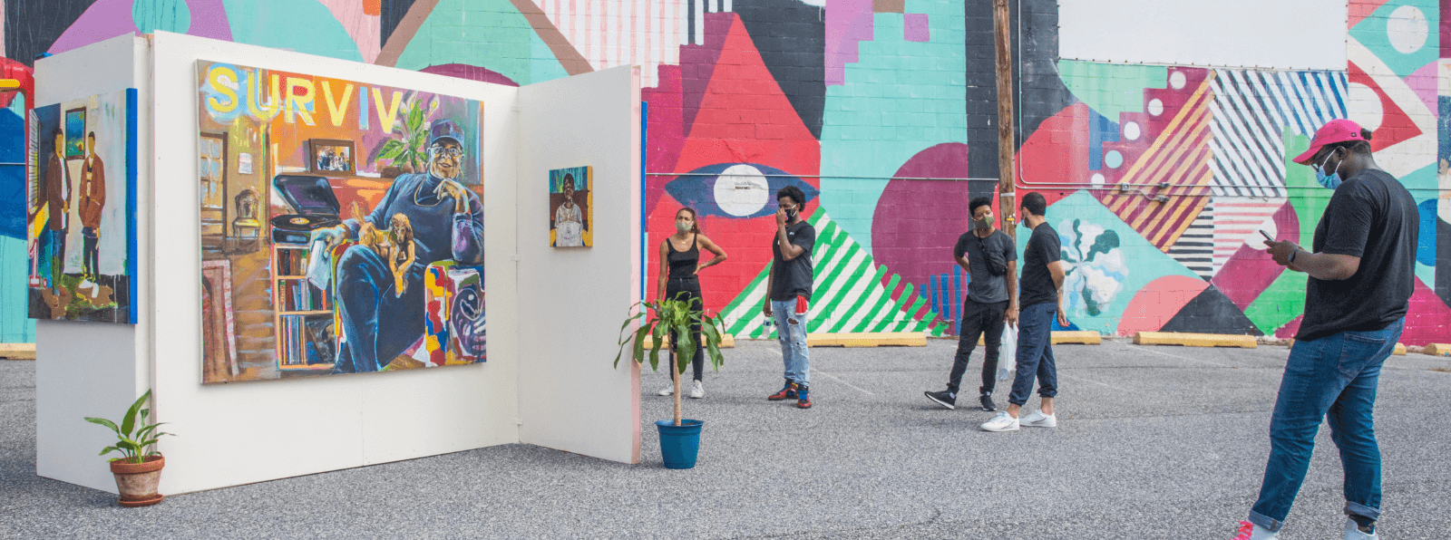 Five people in front of a mural and in a parking lot looking at paintings installed on a free standing white wall